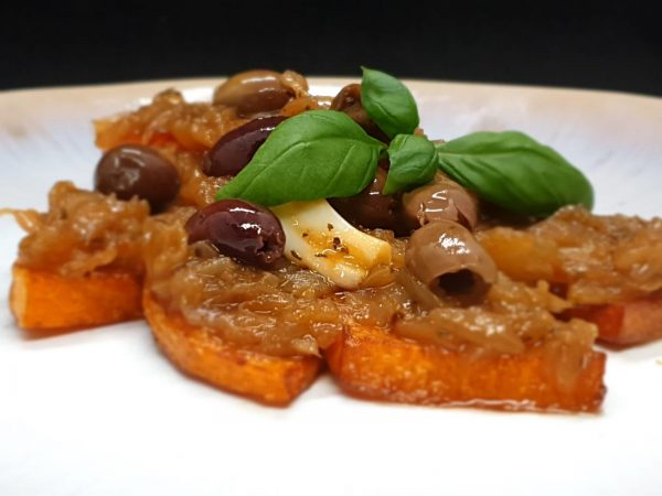 sweet and sour pumpkin with basil leaves and olives on top sicllan food